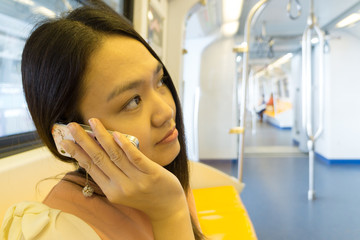 Young lady is calling phone in the sky train