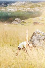 Yogaposen im hohen Gras vor einem Bergsee in den Alpen