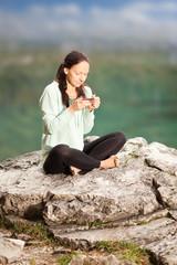 Frau sitzt auf einem Stein und trinkt Tee