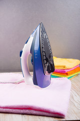Steam iron and  with clothes, on bright backgroundм