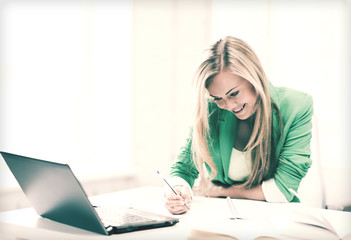 smiling student girl writing in notebook