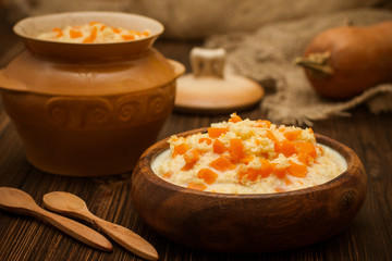 milk porridge with pumpkin and millet in a wooden bowl