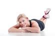canvas print picture - Junge Frau liegt vergnügt auf dem Boden nach Sport