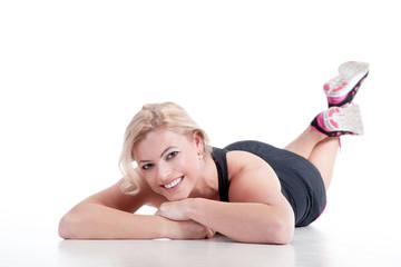 Junge Frau liegt vergnügt auf dem Boden nach Sport