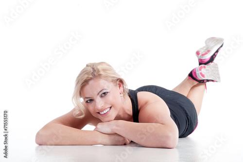 canvas print picture Junge Frau liegt vergnügt auf dem Boden nach Sport