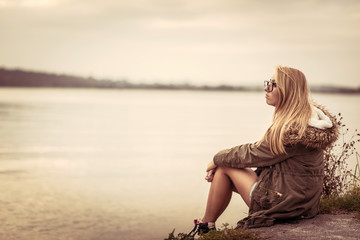Girl sitting near lake in the evening sunset