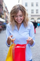 Frau mit blonden Locken schaut in ihre Einkaufstasche