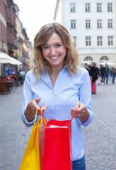 Lachende Frau mit blonden Locken hat eingekauft