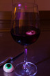 canvas print picture - Halloween eyes in a redwine glass