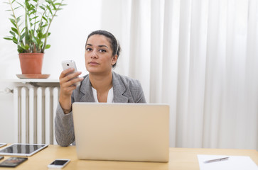 Businesswoman sitting in office ready to give a phone call