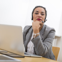Portrait of attractive secretary with headphones looking at came
