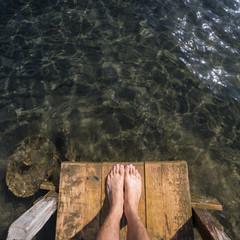 feet on wooden pier