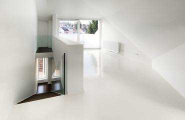 Empty attic room with white epoxy flooring