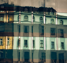 Reflection of old building in modern building in Prague