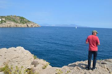 man climbing on rock coast