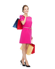 smiling woman in pink dress with shopping bags