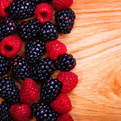 Raspberries and Blackberry on Wooden Background
