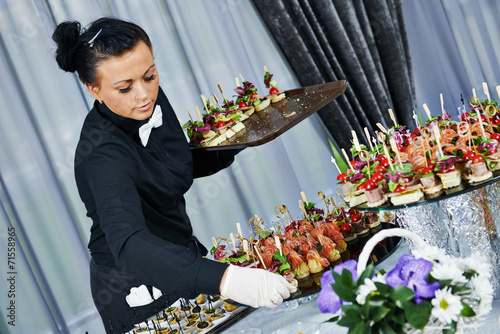 Waiter serving catering table - 71558965