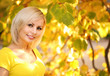 Autumn Cheerful Woman. Blonde Girl and Yellow Leaves. Portrait.