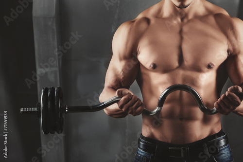 Poster Close up of young muscular man lifting weights
