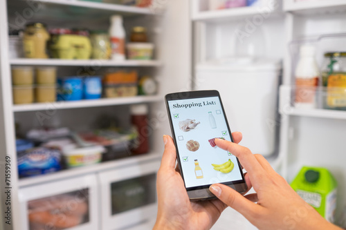 Leinwanddruck Bild Woman makes shopping list on phone connected to the refrigerator