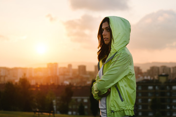 Urban female athlete crossing arms on sunset and city background