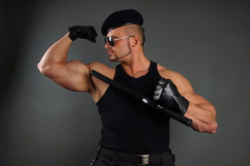 Muscular soldier shows on his biceps with nightstick