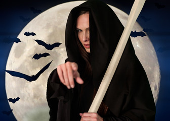 Death with scythe on background of the moon and bats