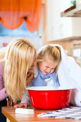 Mutter pflegt krankes Kind mit Dampfbad