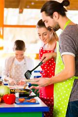 Familie kocht in Küche gesundes Essen