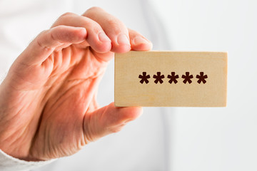 Man holding a wooden block with 5 stars