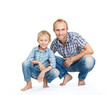 Father with son dressed in jeans and plaid shirts on the white