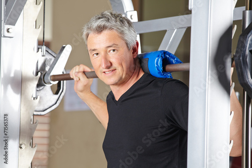 canvas print picture Mann stemmt Langhantel im Fitnesscenter