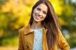 Leinwanddruck Bild - Beautiful elegant woman standing in a park in autumn