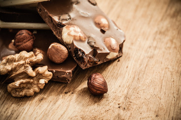 Milk chocolate and hazelnuts on wooden table