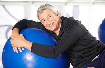 Lächelder älterer Mann mit Gymnastikball
