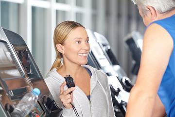Trainerin mit Stoppuhr im Fitnesscenter
