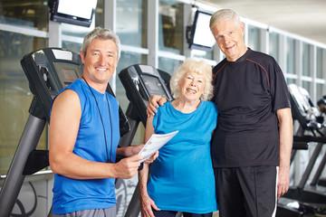 Paar Senioren mit Trainer im Fitnesscenter