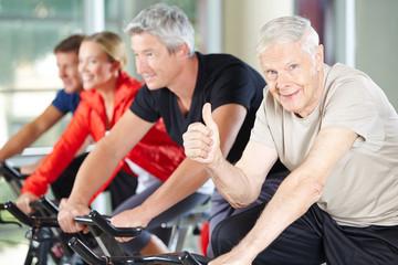 Senior im Fitnesscenter hält Daumen hoch