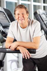 Senior am Laufband im Fitnesscenter