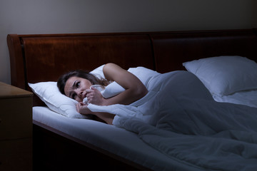 Terrified woman lying in bed