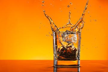 Whiskey drink splashing out of glas