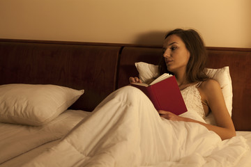 Pesive woman lying alone, reading book