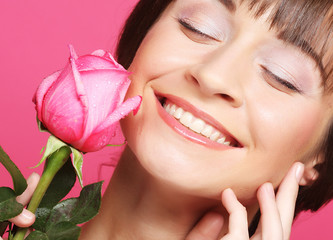 Happy woman holding pink rose