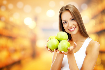 Shopping concept. Beautiful young woman with green apples
