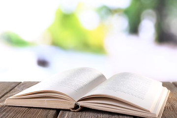 Open book on wooden table on natural background