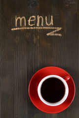Inscription menu on wooden board with cup of tea close-up