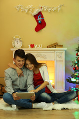 Couple near fireplace in  Christmas decorated house with tablet