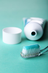 Toothbrush with blue toothpaste on color background