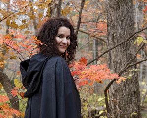 Smiling girl in black mantle in the autumn forest